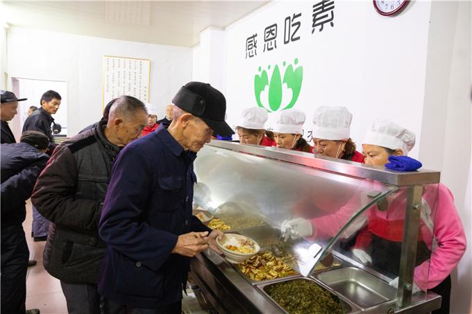 老人们排队领取饭菜。.jpg
